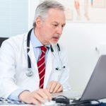 Senior doctor working at his laptop
